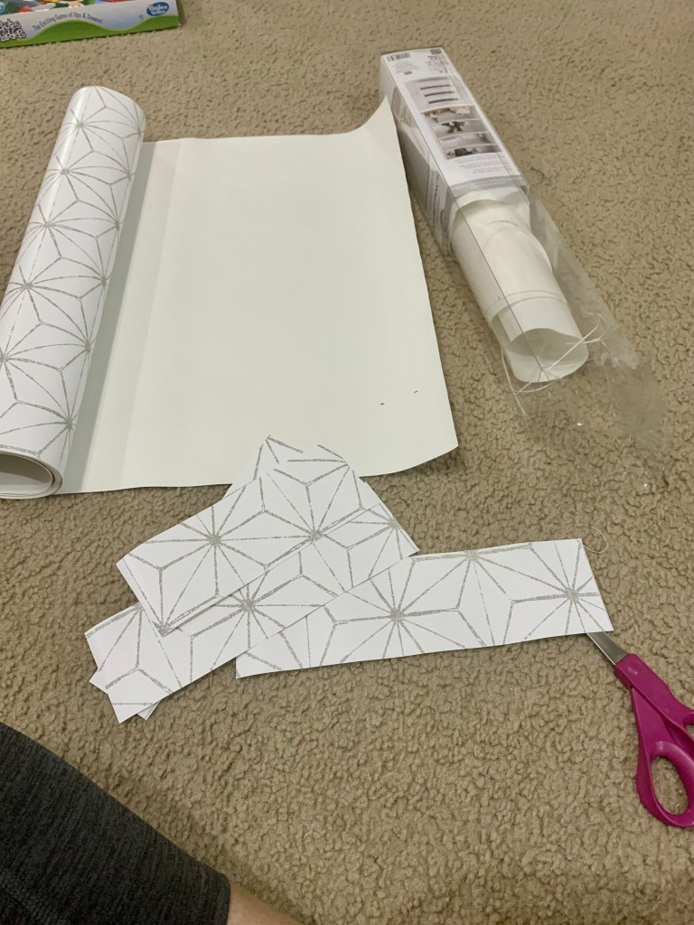Measuring and cutting the wallpaper for the interior of the vintage cabinet.