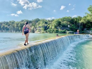 Girl walking along dam at Blue Hole Park in Georgetown, TX.