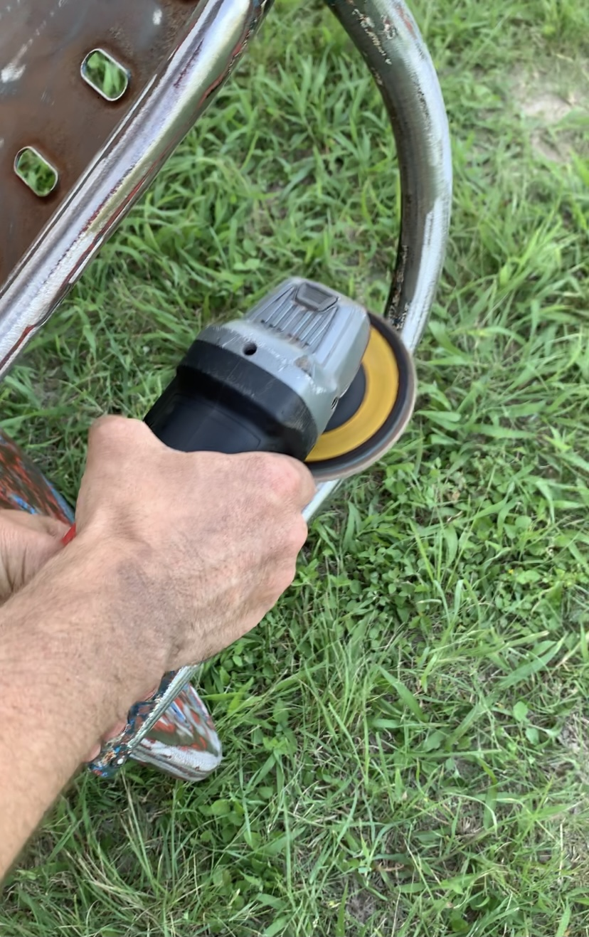 Use an angle grinder and flap disc to remove layers of paint and rust from vintage metal chairs.