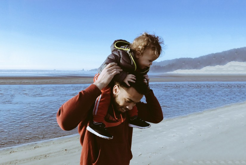 image of man with toddler on his shoulders at the beach