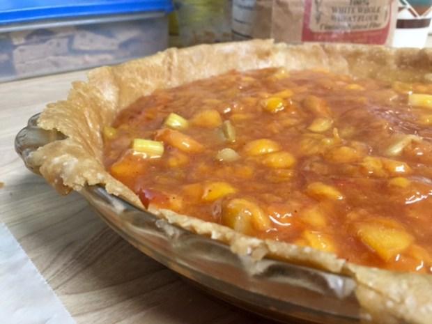 peach rhubarb pie filling in pie closeup