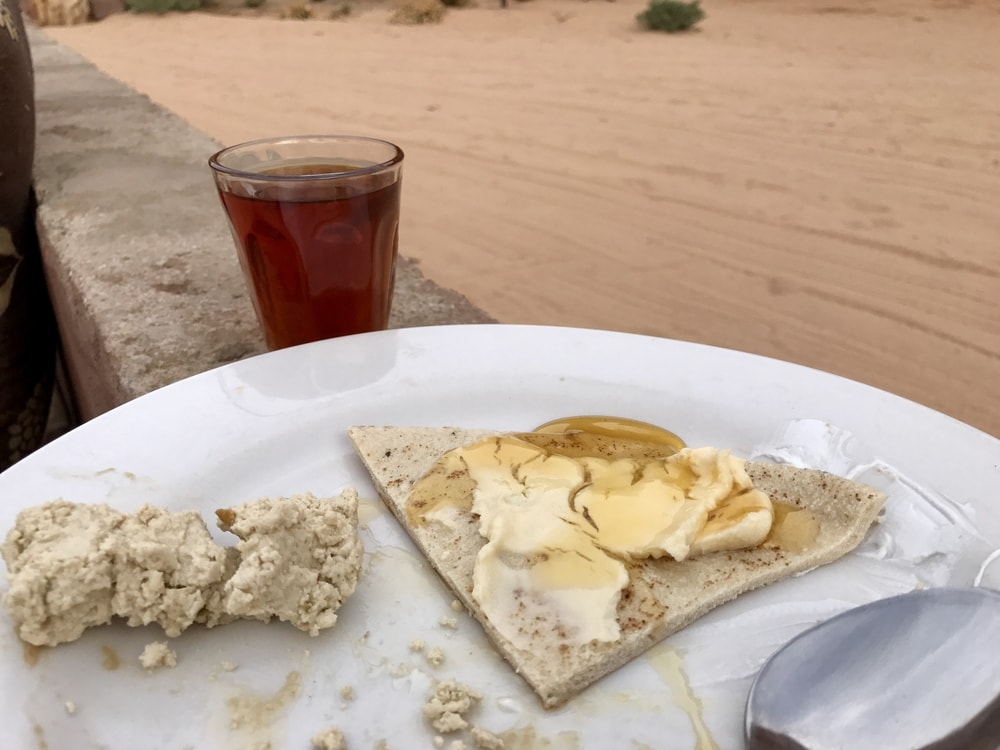 Halva, flatbread and honey, and hot sweet tea for breakfast in a Bedouin camp
