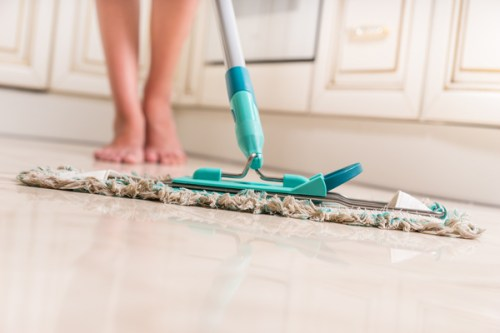 Low Angle View of Young Woman Mopping Kitchen Floor with Focus on Shiny Clean Floor and Mop
