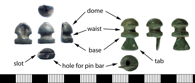 The parts of cruciform brooch knobs. Two separately made side knobs, one half-round with a slot (FAKL-910E67) and the other full-round with a tab (DENO-A9EAE3).