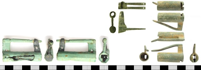 Three examples of tubular padlocks. Bottom left, BERK-A8A8A1, with the two halves made from metal of very different colours; this example has a T-shaped keyhole in the end of the case. Top centre, SF-BF1DC4 (bolt and arm only); the holes at the end of the spines are for fixing the springs. Right: SWYOR-3D0FA8, with a T-shaped keyhole partly in the end and partly on the underside of the case.