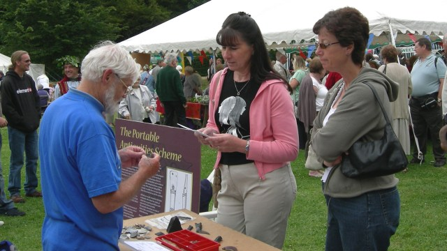 A Finds Liaison Officer identifies small finds for members of the public on a stall at a village fair