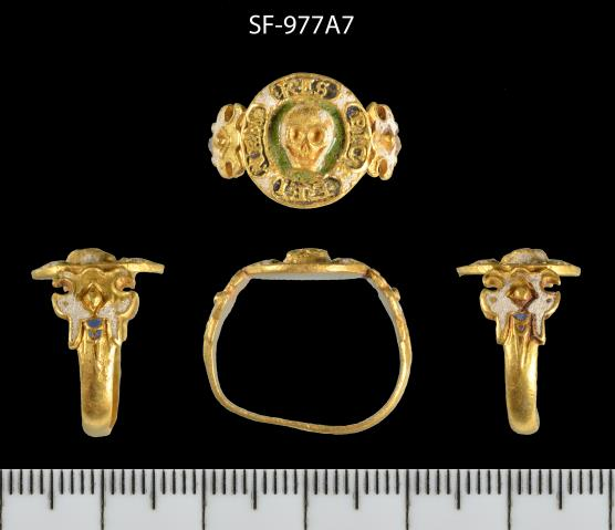 An image showing 4 views of a gold ring. The topmost view shows the front of the bezel, which is decorated with a grinning skull. Beneath it are 3 views showing the top of the ring and either side.