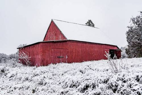 A red barn covered in a winter blanket of snow.