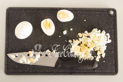 Когда сварятся куриные яйца, чистим их и нарезаем кубиком