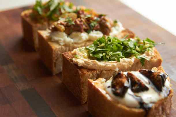 Four slices of toasted bread with various toppings.