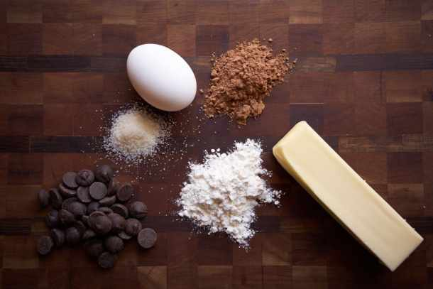 Chocolate chips, flour, cocoa powder, sugar, an egg, and a stick of butter displayed on a wooden cutting board.
