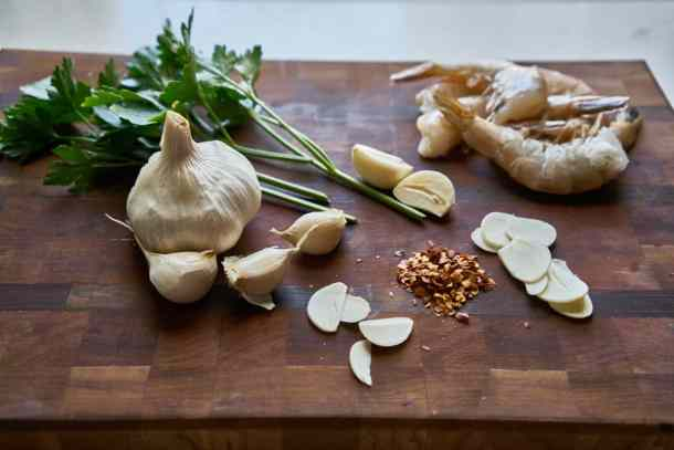 Parsley, a head of garlic, thinly sliced garlic cloves, crushed red pepper, and raw shrimp are displayed on a wooden cutting board.