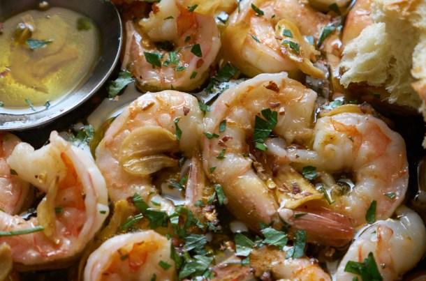 Close up of garlic shrimp (gambas al ajillo) with a silver serving spoon.