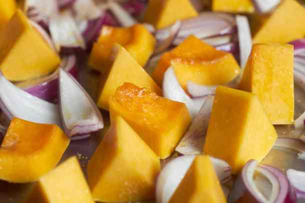 Chopped butternut squash and red onions coated with olive oil on a silver sheet pan.