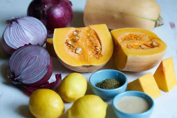 A butternut squash cut in half is surrounded by a halved red onion, whole lemons, and small blue bowls filled with za'atar and tahini.