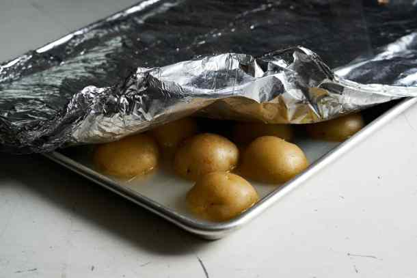 Yukon gold potatoes cut in half on a sheet tray filled with a shallow amount of water after baking tightly covered with foil, ready to be made into crispy roasted potatoes.