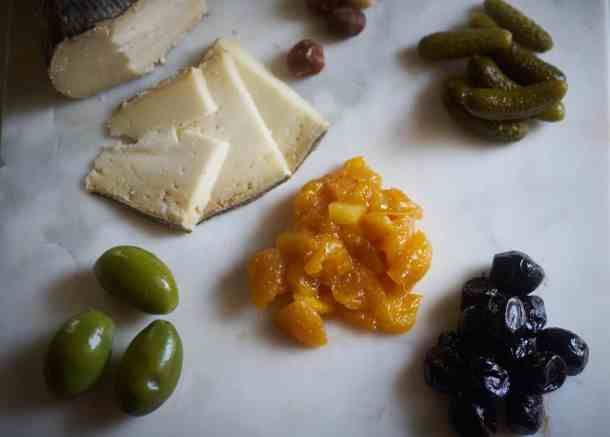 A variety of ingredients for a cheese plate including mostarda, olives, pickes, hazelnuts and cheese, on a marble surface.