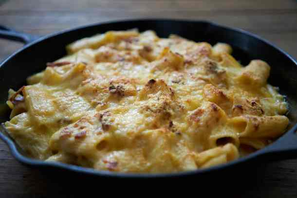 Creamy pasta with bacon and comté cheese (Pâtes aux lardons et comté) in a cast iron pan on a wooden table. The cheese on top is golden brown.