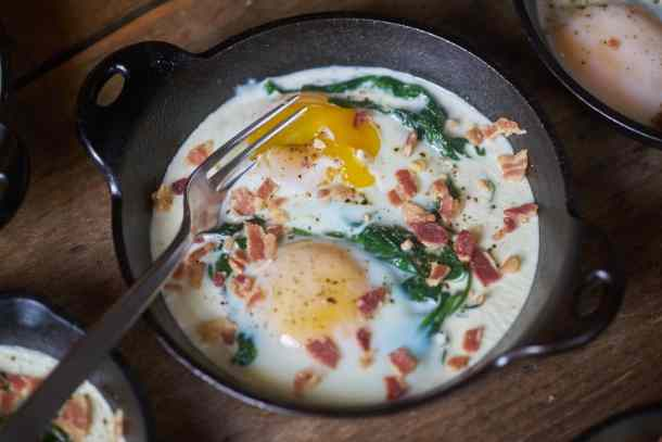 Eggs en cocotte with spinach and bacon in a small cast-iron serving dish with a fork that has broken open the egg yolk. The dish is displayed on a wooden surface.