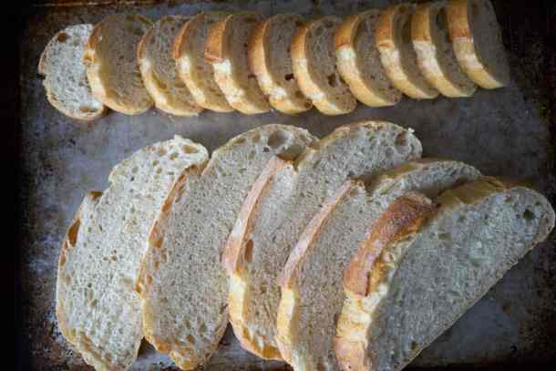 Slices of baguette and sourdough bread are laid out in rows on a baking sheet.