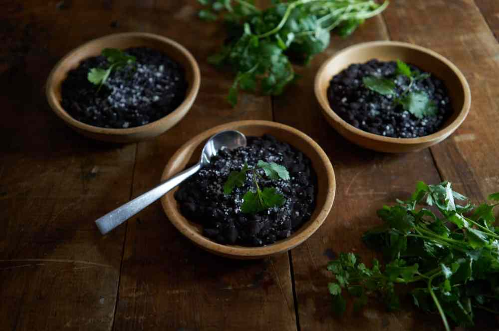 3 wooden bowls of Mexican black beans, a sliced avocado, and fresh cilantro on a wooden table.
