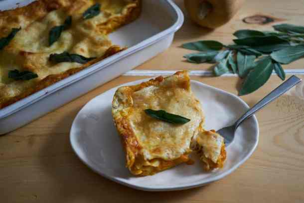 A portion of butternut squash lasagna with a fork on a white plate. A white baking dish filled with the lasagna and fresh sage are in the background.