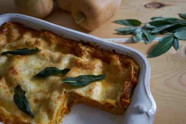 Butternut squash lasagna  garnished with fried sage leaves in a white baking dish. Fresh sage and whole butternut squash are in the background.