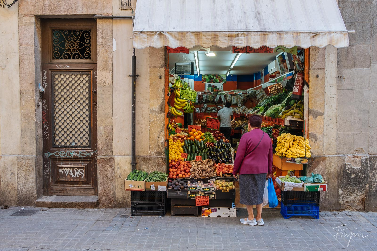 An old woman is shopping for fruits