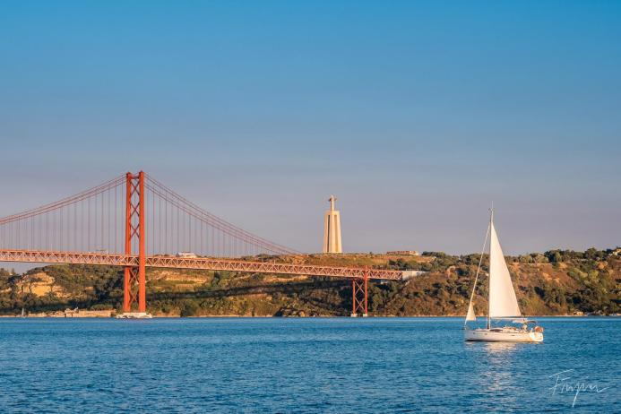 lisbon bridge sunset sailing boat