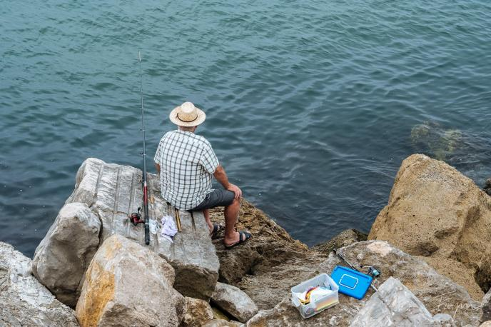 guy sitting fishing nazare