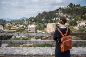 A girl is enjoying the view over ra small village on the island of Mallorca