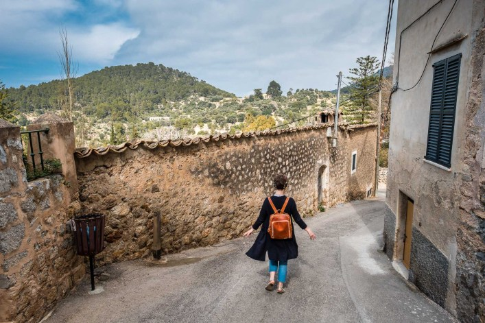 A girl with a leather backpack walks down an alley at sunshine in a village on the island of Mallorca