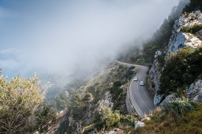 Two white cars on a foggy and winding road in the mountains of the island of Mallorca