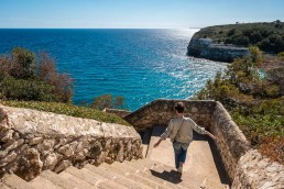 A girl is going down a stone staircase which is leads down to the blue ocean on the island of Mallorca