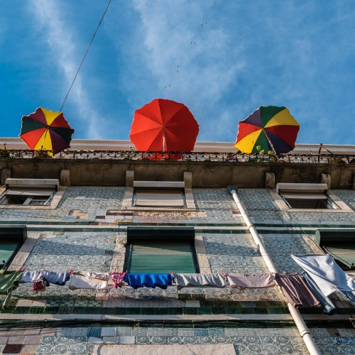 Colourful umbrellas against the blue sky in the city of Lisbon in Portugal