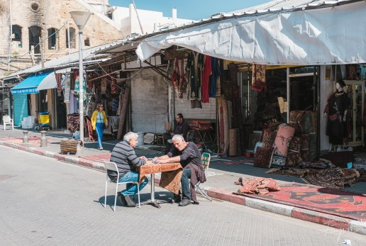 Two old man sitting in a street in Tel Aviv at a table playing cards