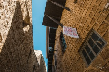 Standing in an alley in Tel Aviv looking at the blue sky