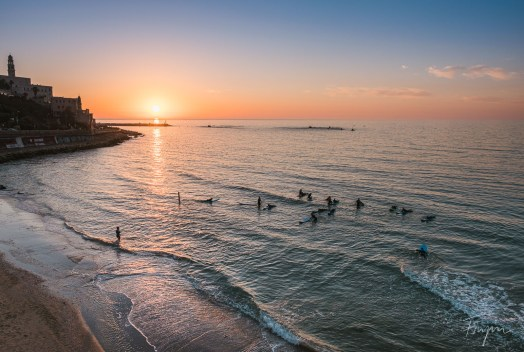 People swimming and surfing in the ocean at sunset in Tel Aviv