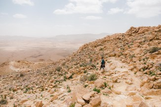 A girl is hiking down a path to the bottom of the Makhtesh Ramon