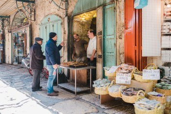 Four men talk in front of a bakery in the old down of Jerusalem