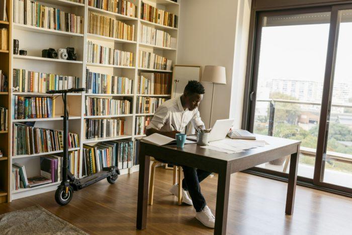رجل يجلس في شقة أمام جهاز كمبيوتر محمول على مكتب فيه كتب وأوراق.