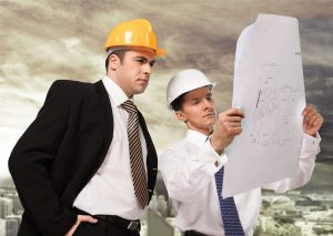men in ties with hard hats looking at construction plans