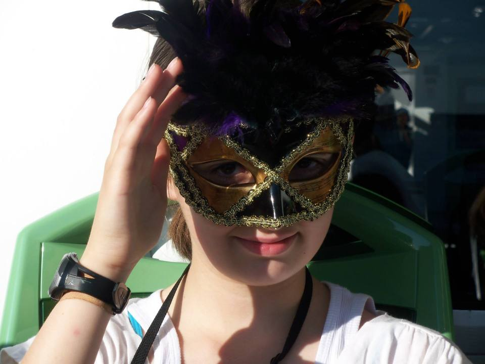A selfie of me wearing an elaborate Venetian mask with feathers at the top.