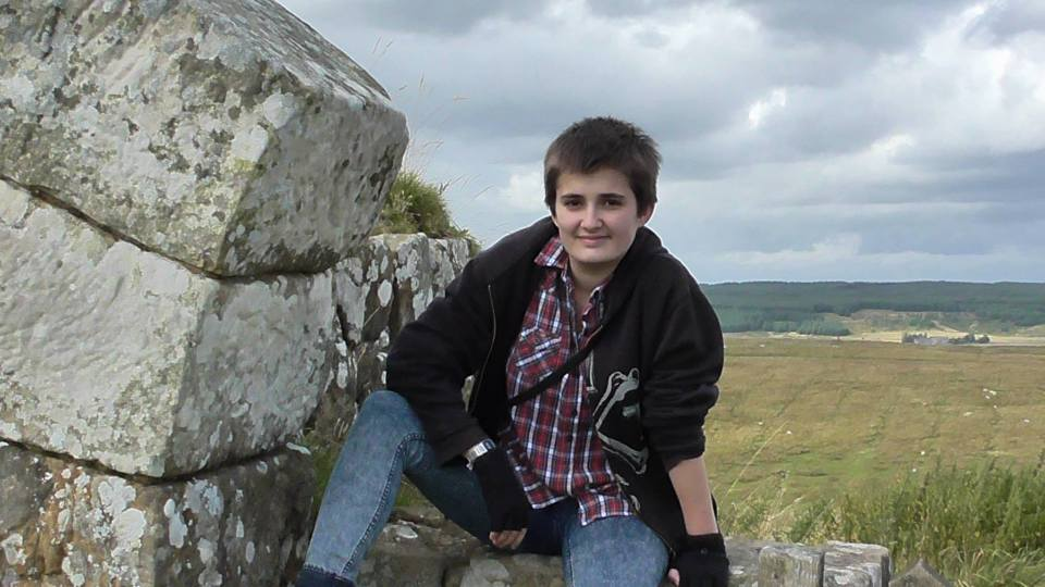 A photo of me sitting on a milecastle at Hadrian's Wall, with short fluffy hair and a plaid shirt.