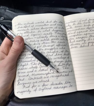 Photo of an open notebook and pen with joined-up writing