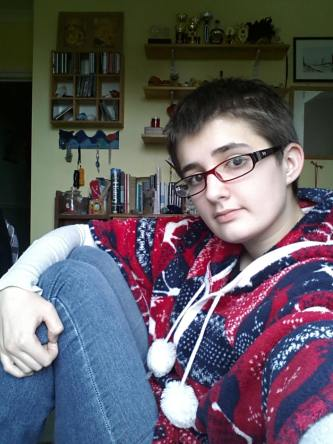 A selfie of me at eighteen. I'm side-on to the camera, sitting with my knees up. I have a slightly messy pixie cut and glasses with a red and black plastic frame. I'm wearing a blue and red blanket poncho over a long-sleeved shirt and jeans; I'm hugging my knees with one arm.