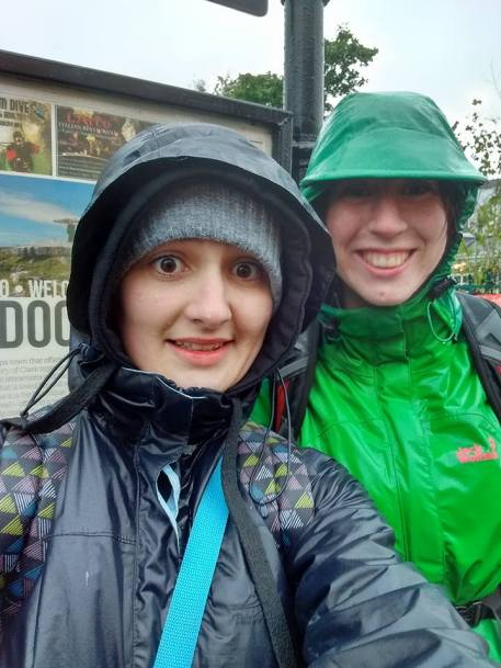 """A selfie of me and my friend Caspian standing in front of the """"Lisdoonvarna"""" sign in Lisdoonvarna, Co. Clare. We are both wearing raincoats and are clearly soaked to the skin, but we're smiling triumphantly."""