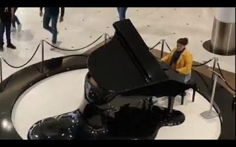 Una mujer toca el 'Cara al Sol' en el piano de un centro comercial