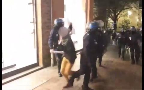 Un antidisturbios francés le hace la zancadilla a una manifestante justo después de que uno de sus compañeros la empujase