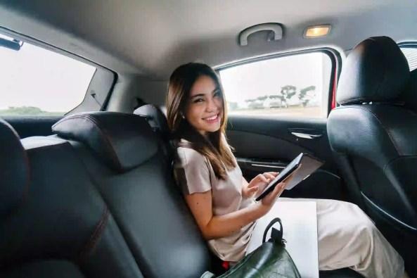 smiling woman sitting inside car